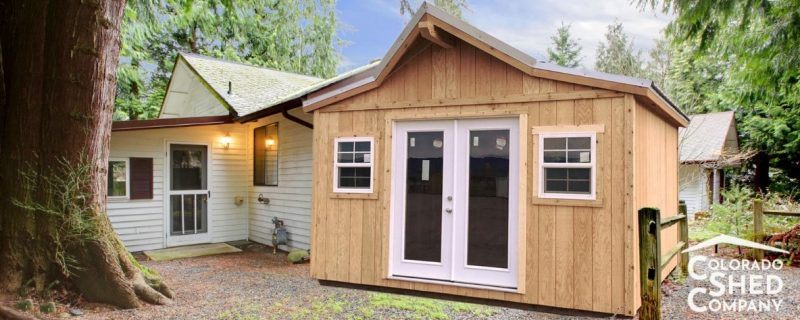 A Western Shed Built With Stained wood with a Double Door and 2 Windows on the side in Canon City