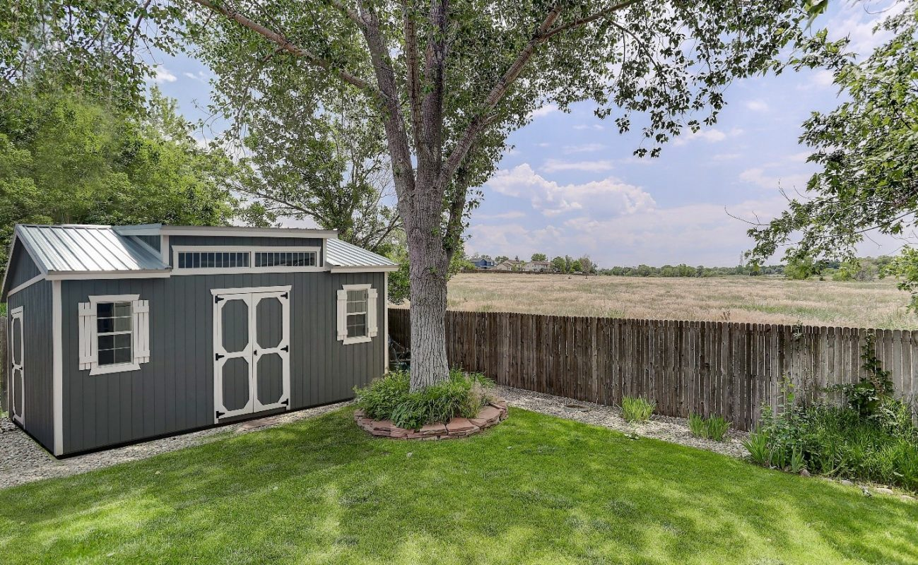 Green Shed With 2 Windows and 1 Dormer with Double Door in a backyard in Canon City.