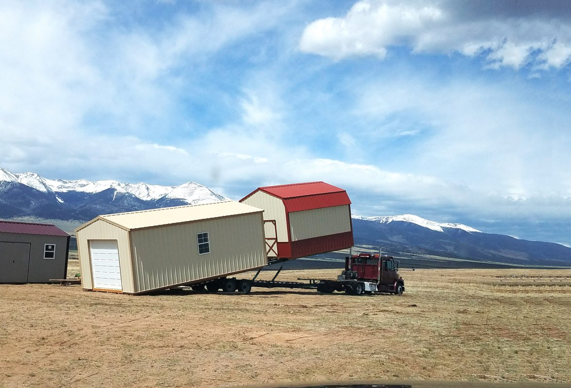 A shed and A garage being delivered to the location in Canon City